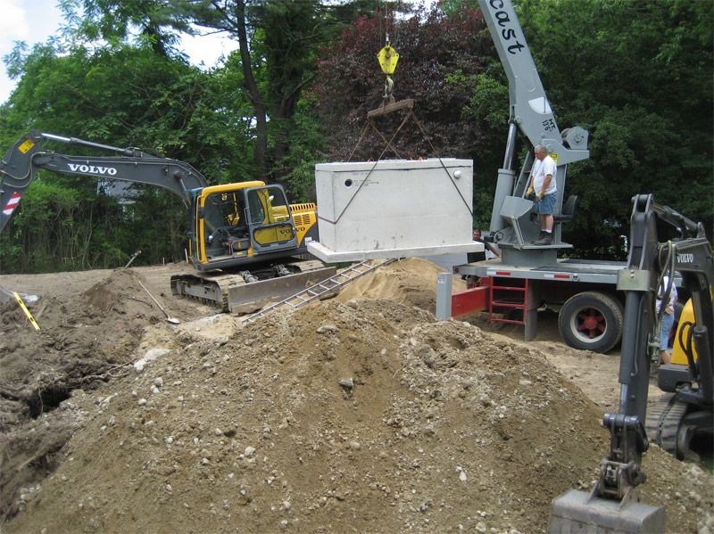 Septic tank being installed with heavy equipment and crane
